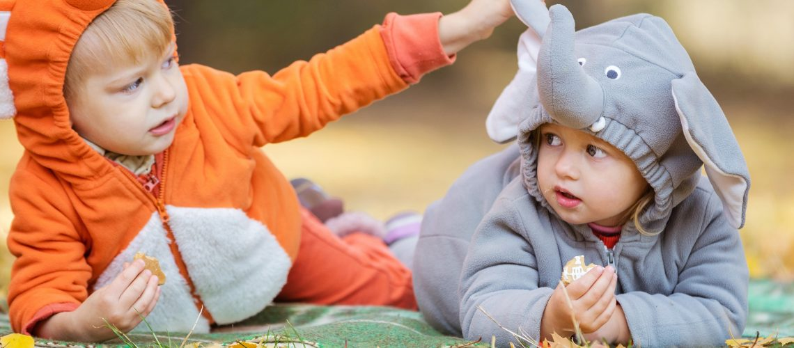 Little children in animal costumes, boy dressed as fox, girl as elephant, playing in autumn forest