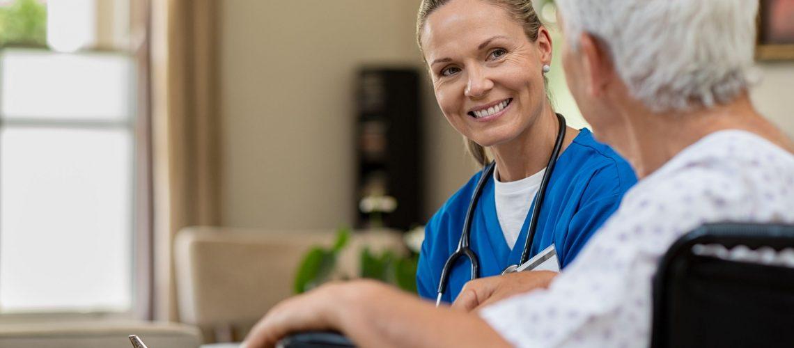 friendly-nurse-talking-to-senior-patient-Q58Y9GB