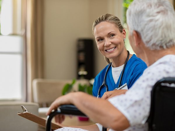 Friendly doctor examining health of patient sitting in wheelchair. Happy smiling nurse consulting disabled patient about treatment. Nurse caring about elder handicap man at home.